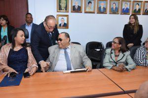 Director General saludando a funcionario con discapacidad