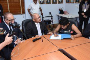 Foto de funcionaria con discapacidad firmando su designación en presencia del Director General