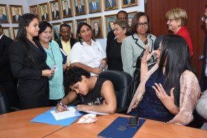 Foto de funcionaria con discapacidad firmando su designaciónn