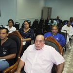 Personas sentadas escuchando atentos en la reunión
