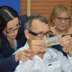 Prueba de lentes con persona de discapacidad visual identificando papel moneda